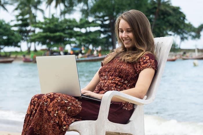 Hübsches Mädchen am Strand mit Laptop